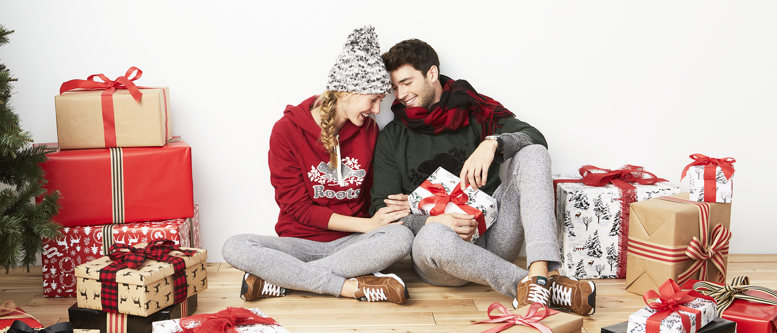 Hero image - Couple unwrapping presents beside a christmas tree
